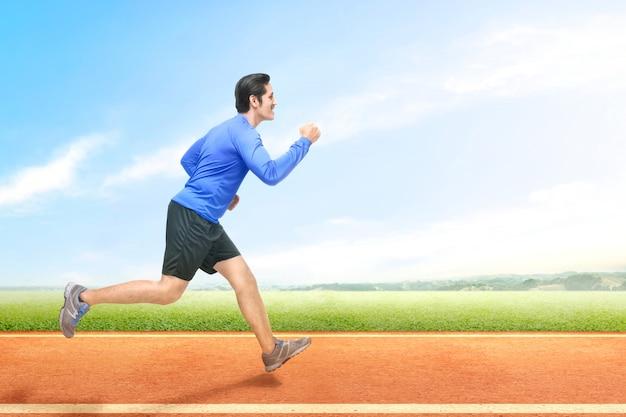Asiatischer läufermann, der auf der laufbahn läuft Premium Fotos