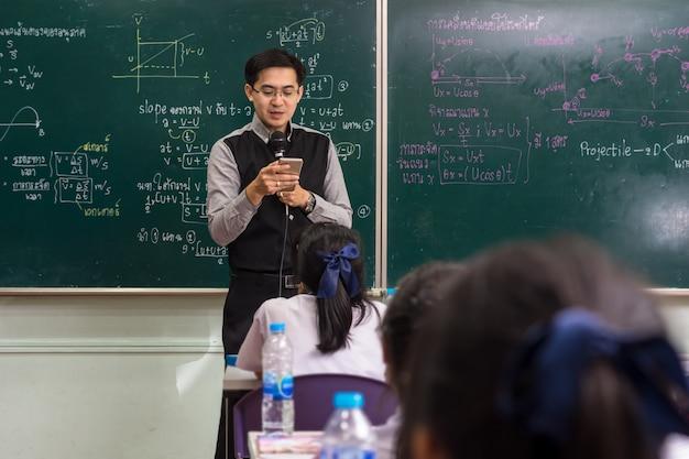 Asiatischer lehrer, der das intelligente mobiltelefon verwendet, um lektion über die physikformel zu geben Premium Fotos