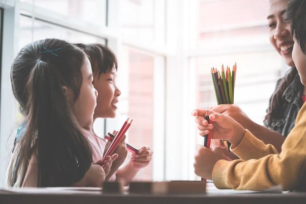 Asiatischer lehrer unterrichtet kinder im kindergartenklassenzimmer Premium Fotos