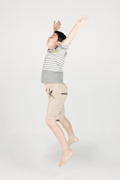 Asiatischer lustiger kinderjunge, der auf grauen hintergrund springt. Premium Fotos
