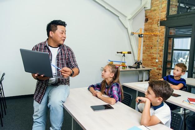 Asiatischer männlicher lehrer sitzt mit laptop in händen auf schreibtisch und erklärt unterricht für sechs grundschüler. schulkinder sitzen an schreibtischen und hören ihrem dozenten zu. Premium Fotos