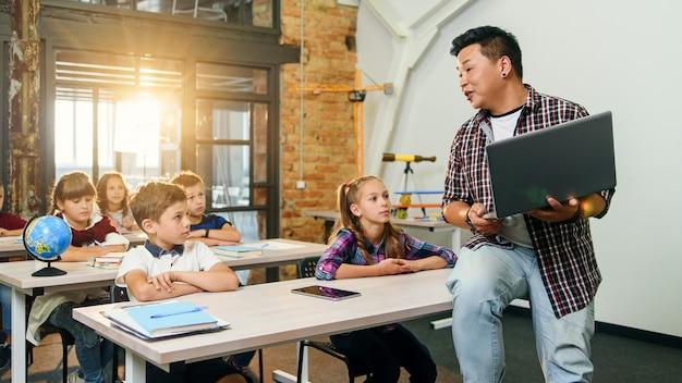 Asiatischer männlicher lehrer sitzt mit laptop in händen auf schreibtisch und erklärt unterricht für sechs grundschüler Premium Fotos