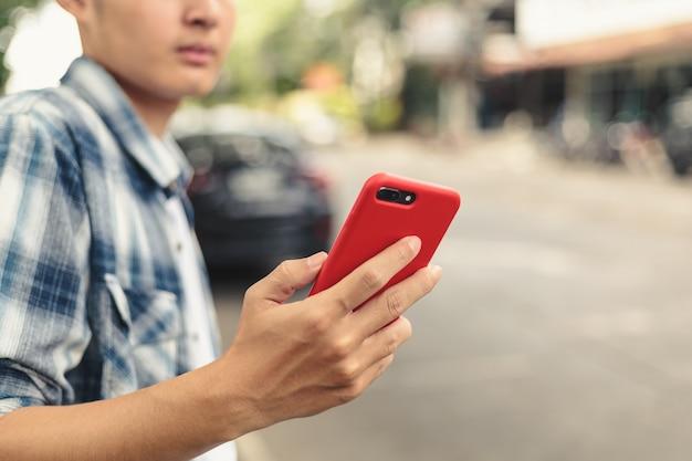 Asiatischer mann, der auf uber taxi wartet Premium Fotos