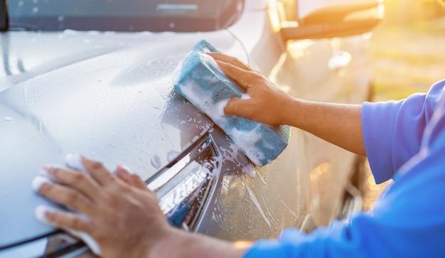 Asiatischer mann, der blauen schwamm mit seife verwendet, um das auto an im freien in der sonnenuntergangzeit zu waschen Premium Fotos