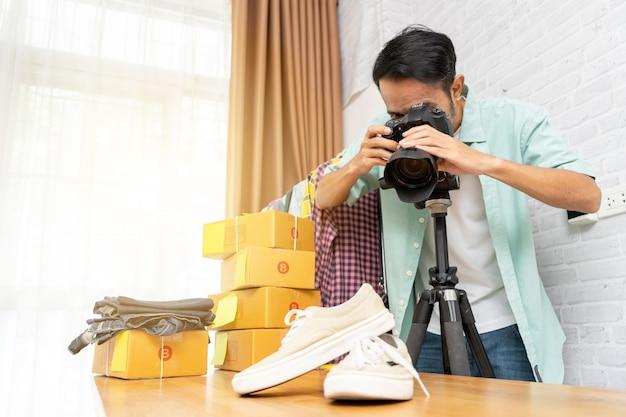 Asiatischer mann, der den schuhen mit digitalkamera für beitrag zum online-verkauf foto macht Premium Fotos