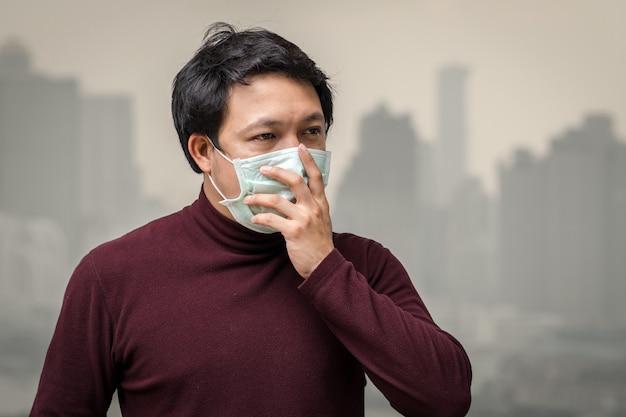 Asiatischer mann, der die gesichtsmaske gegen luftverschmutzung am balkon der hohen wohnung trägt Premium Fotos