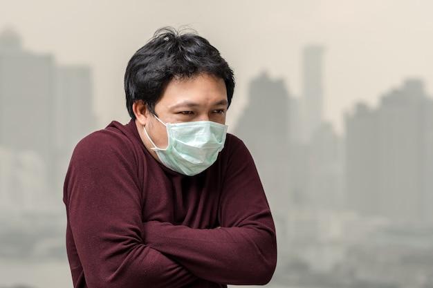 Asiatischer mann, der die gesichtsmaske gegen luftverschmutzung mit kälte am balkon trägt Premium Fotos