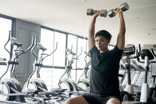 Asiatischer mann, der dummkopf hält und für das spielen der schulterpresse zum gewinnen des muskels an der turnhalle anhebt Premium Fotos