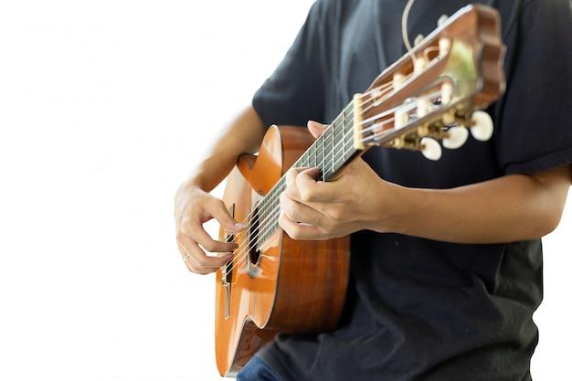 Asiatischer mann, der eine klassische gitarre lokalisiert auf schwarzem hintergrund spielt. Premium Fotos