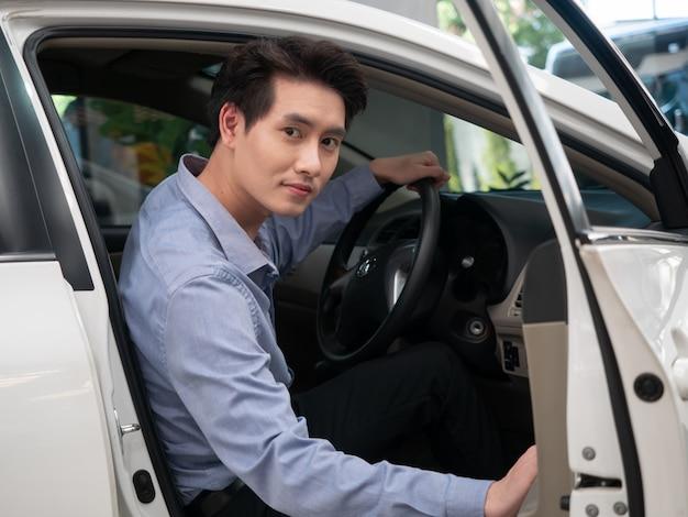 Asiatischer mann, der im neuen auto sitzt und autoschlüssel zeigt. junger attraktiver mann, der salonauto sitzt und offenes fenster schaut. Premium Fotos