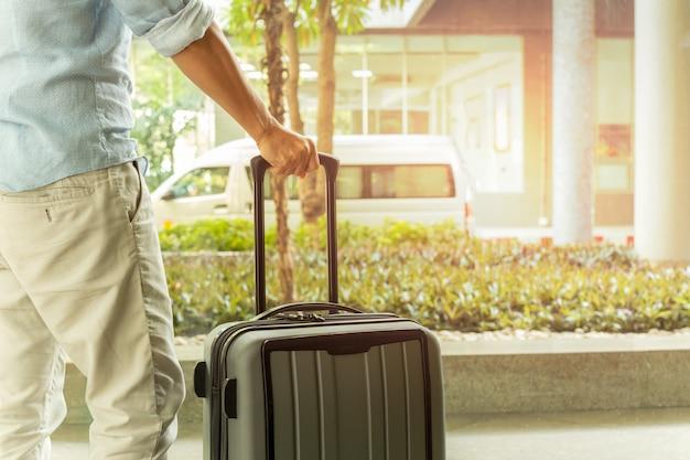 Asiatischer mann, der mit koffergepäck im flughafenterminalreisekonzept steht. Premium Fotos