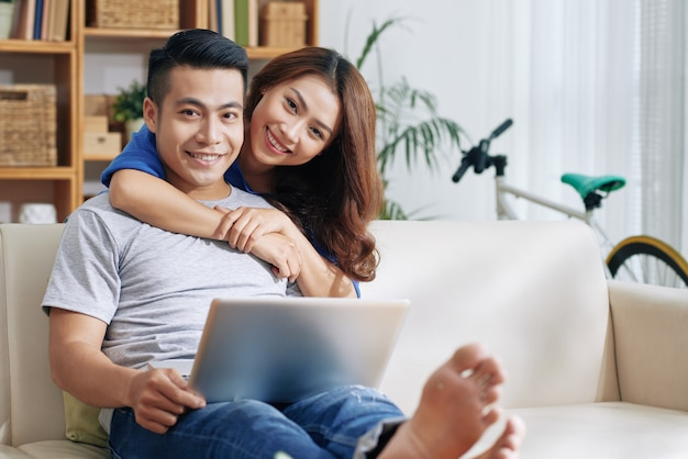 Asiatischer mann, der sich zu hause auf couch mit laptop und glücklicher frau umarmt ihn entspannt Kostenlose Fotos