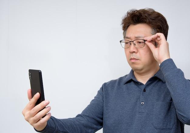 Asiatischer mann, der versucht, etwas an seinem handy zu lesen. schlechte sicht, presbyopie, myopie. Premium Fotos