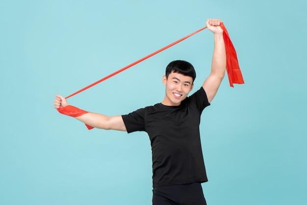 Asiatischer mann des athleten, der durch die verwendung des widerstandbandes vor übung aufwärmt Premium Fotos