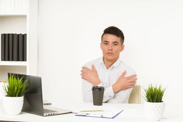 Asiatischer mann friert im büro ein, da die heizung oder kühlung der klimaanlage übermäßig unterbrochen ist Premium Fotos