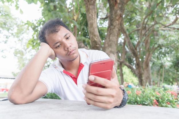 Asiatischer mann fühlt sich gelangweilt und trauriger moment mit handy. er wartet etwas vom handy ab. Premium Fotos