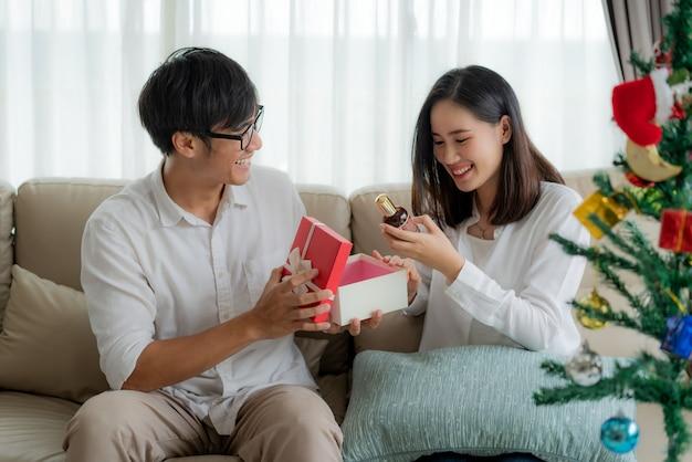 Asiatischer mann geben der frau eine rote geschenkbox, in der sich eine flasche parfüm befindet. Premium Fotos