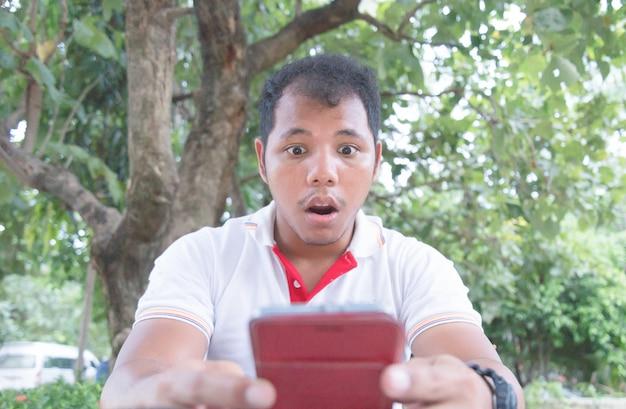 Asiatischer mann glaubt schock- und überraschungsmoment mit handy im park Premium Fotos