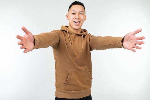 Asiatischer mann im braunen kapuzenpulli mit offenen armen Premium Fotos