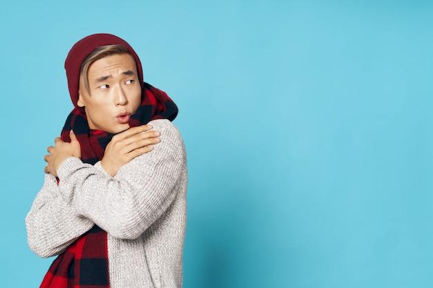 Asiatischer mann in der warmen winterkleidung, die aufwirft Premium Fotos