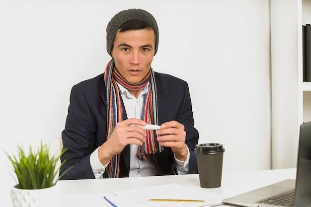 Asiatischer mann in einem hutschal und einer jacke messen die temperatur mit einem thermometer im büro Premium Fotos