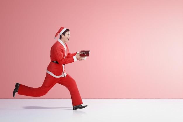 Asiatischer mann in laufendem sankt-kostüm beim halten der geschenkbox Premium Fotos