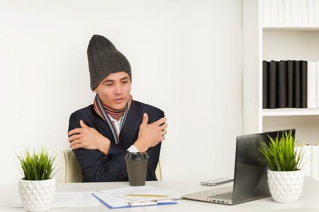 Asiatischer mann in mütze, schal und jacke friert im büro seit kaputter heizung oder kühlung der klimaanlage übermäßig ein Premium Fotos
