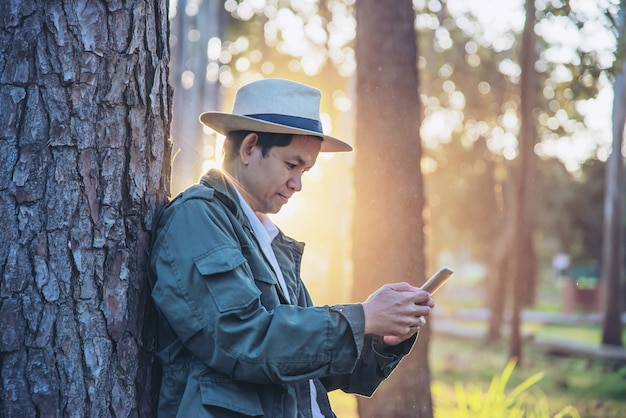 Asiatischer mann mit handy in der waldbaumnatur - natur und technologiekonzept der leute im frühjahr Kostenlose Fotos
