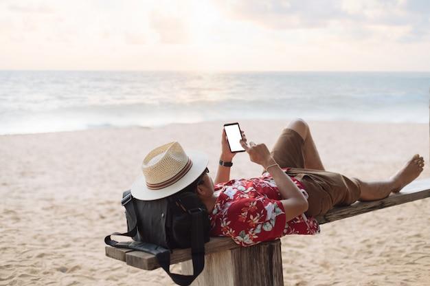 Asiatischer mann mit smartphone am strand liegen Premium Fotos