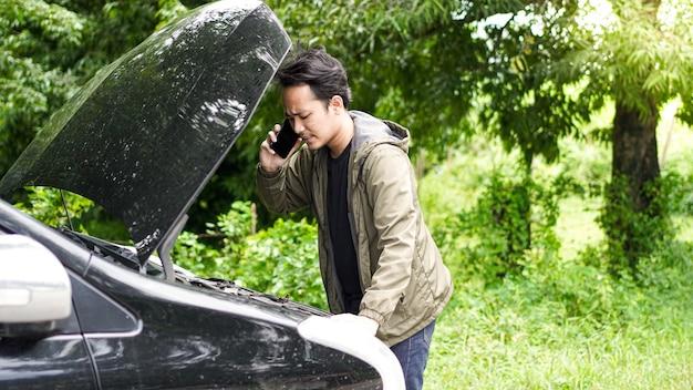 Asiatischer mann öffnete die motorhaube des autos, während er anrief Premium Fotos