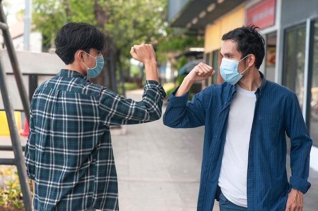 Asiatischer mann schüttelt hand kein berührungskonzept neue normale soziale distanzierung, draußen Premium Fotos
