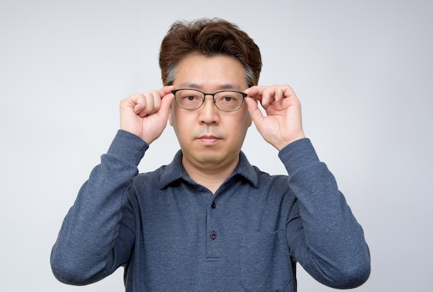 Asiatischer mann von mittlerem alter, der versucht, gläser auszuziehen und etwas zu sehen. schlechte sicht, presbyopie, myopie. Premium Fotos