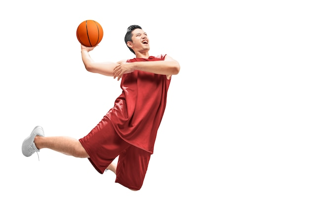Asiatischer mannbasketballspieler springen in die luft mit der kugel Premium Fotos