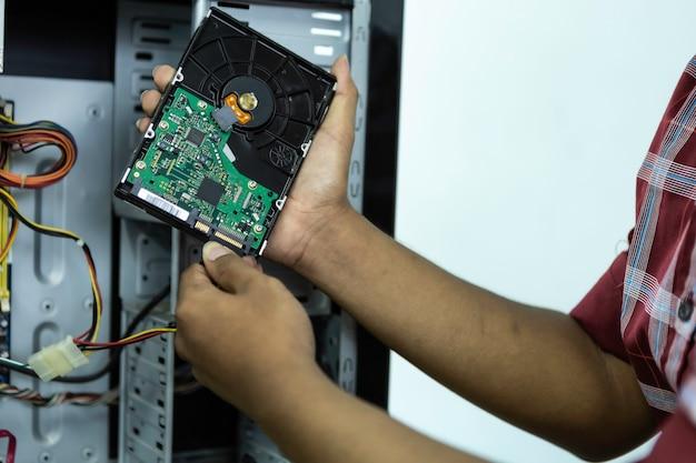 Asiatischer manncomputertechniker schraubenzieher-computer-motherboard-reparatur-sicherheitsausrüstung ist gläser. gerät durch computer. Premium Fotos