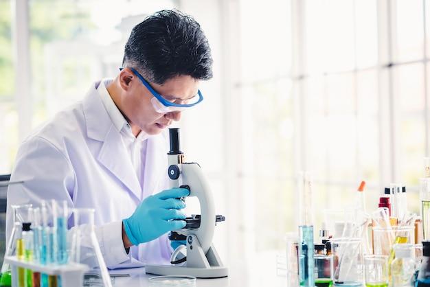 Asiatischer mannwissenschaftler, der in einem labor mit mikroskop arbeitet Premium Fotos