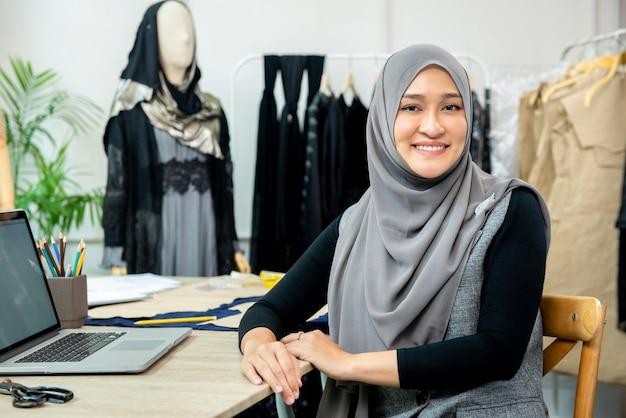 Asiatischer moslemischer frauendesigner in ihrem schneidershop Premium Fotos