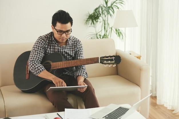 Asiatischer musiker, der zu hause auf couch mit gitarre sitzt und tablette verwendet Kostenlose Fotos