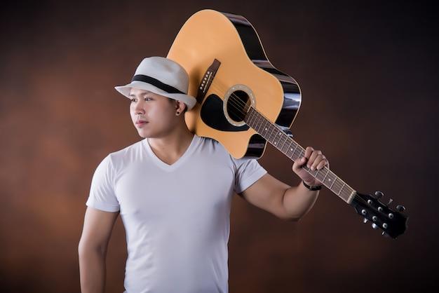 Asiatischer musiker des jungen mannes mit akustikgitarre Kostenlose Fotos