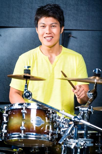 Asiatischer musikerschlagzeuger im tonstudio Premium Fotos