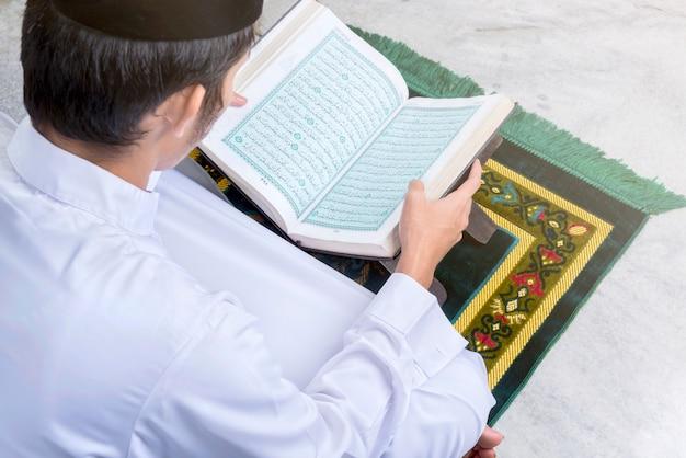 Asiatischer muslimischer mann, der den koran sitzt und liest Premium Fotos