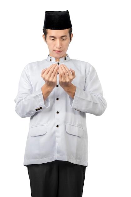 Asiatischer muslimischer mann stehend, während erhobene hände und beten Premium Fotos