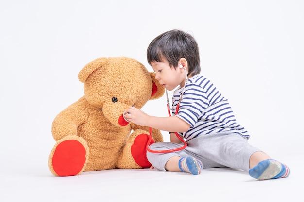 Asiatischer netter junge, der ein doktorgebrauchsstethoskop überprüft den großen teddybären sitzt auf boden spielt Kostenlose Fotos