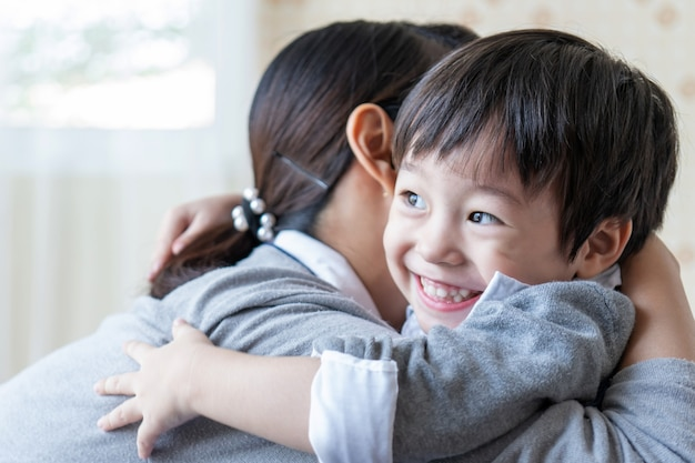 Asiatischer netter junge, der mit glücklich lächelt und zu hause mit mutter, familienkonzept umarmt Kostenlose Fotos