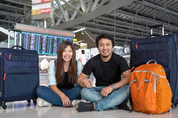 Asiatischer paarreisender, der mit gepäck über dem flugbrett für abfertigung sitzt Premium Fotos