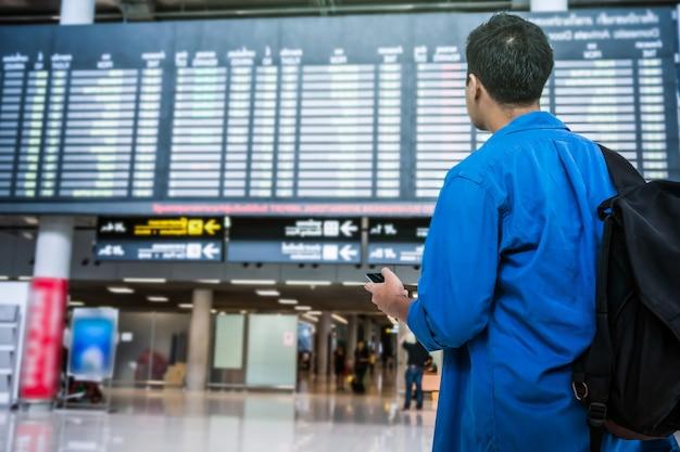 Asiatischer reisender, der das intelligente mobiltelefon für das einchecken am fluginformationsschirm verwendet Premium Fotos
