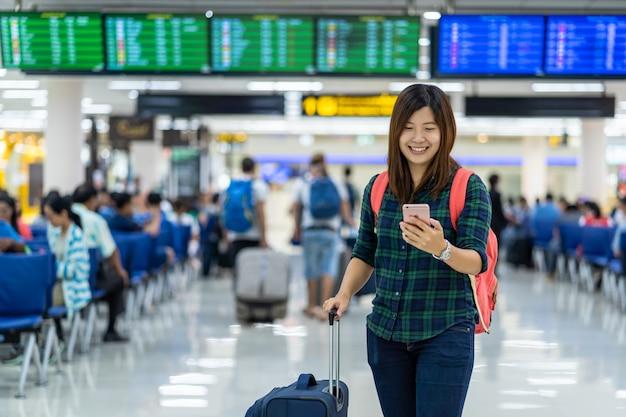 Asiatischer reisender mit dem gepäck, das den intelligenten handy für abfertigung über dem flug bo hält Premium Fotos