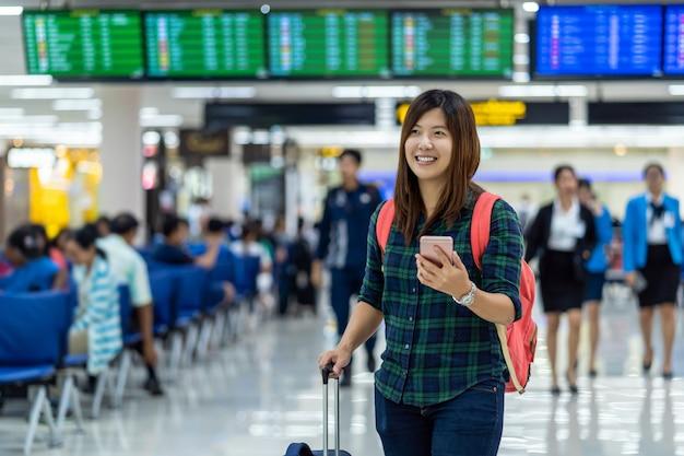 Asiatischer reisender mit dem gepäck, das den intelligenten handy für abfertigung über dem flugbrett hält Premium Fotos