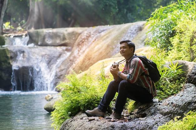 Asiatischer reisendmann mit dem rucksack, der kamera mit grünem natürlichem hintergrund hält. Premium Fotos