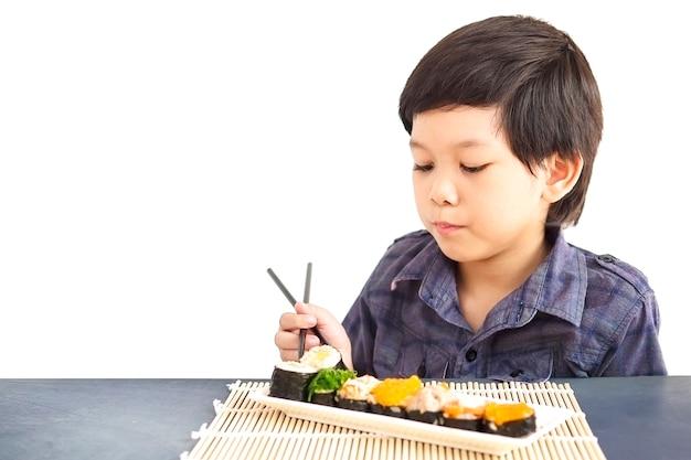 Asiatischer reizender junge isst die sushi, die über weißem hintergrund lokalisiert werden Kostenlose Fotos