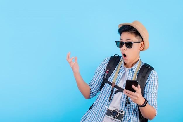 Asiatischer rucksacktourist ist auf einem blauen hintergrund schockiert Premium Fotos